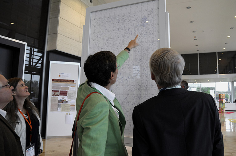 Two people looking at the signatures on the back of a big vertical jigsaw puzzle
